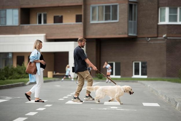 Para spacerująca z psem w pełnym ujęciu
