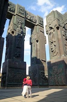 Para spoglądająca w górę na filary kroniki gruzji, oszałamiający pomnik położony w pobliżu tbilisi w gruzji