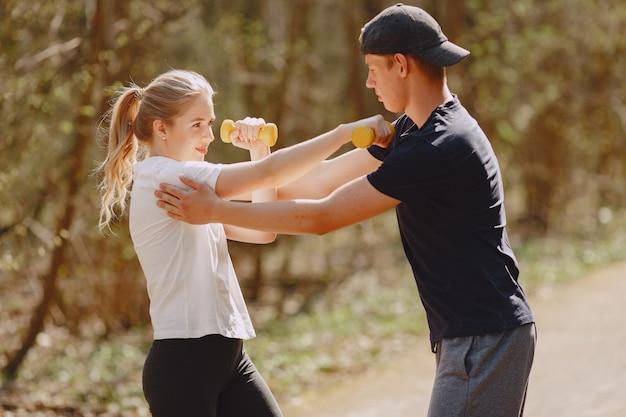 Para sportowa trenuje w letnim lesie