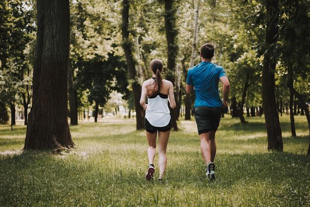 Para sportowców biegnie w parku razem.