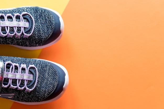 Para sportowych butów do biegania na białym tle na jasnej pomarańczowej ścianie.
