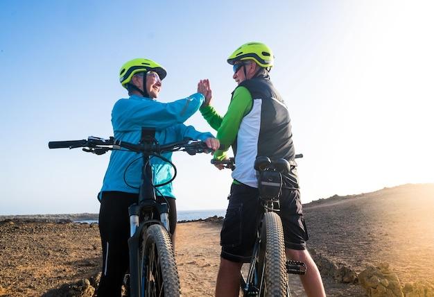 Para starszych dziadków cieszy się życiem na świeżym powietrzu z rowerem elektrycznym. zdrowy styl życia dla osób starszych