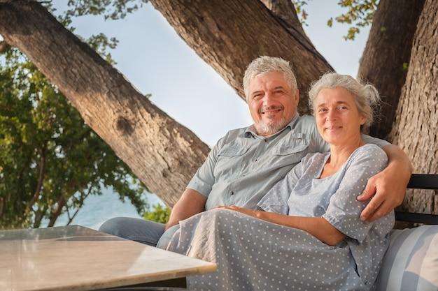 Para starszych na wakacjach w restauracji z widokiem na morze. mężczyzna i kobieta siedzą przy stole