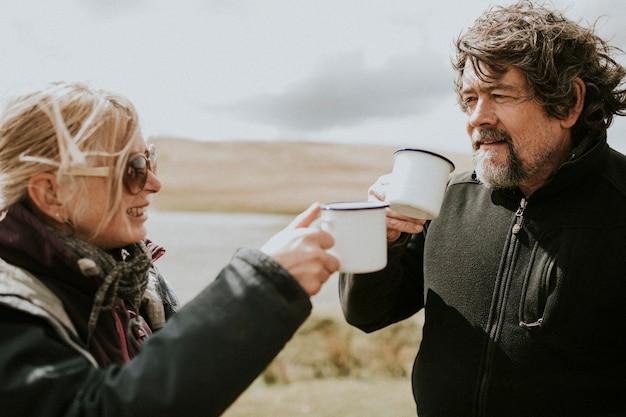 Para starszych obozowiczów pije poranną kawę na wsi