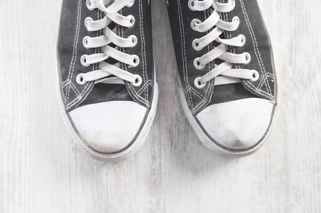 Para starych brudnych butów na białym stole.