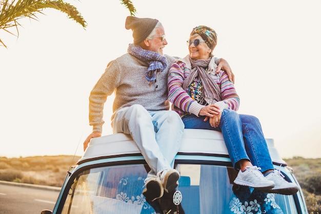 Para Starych Seniorów Siada Razem Na Dachu Furgonetki, Ciesząc Się Zachodem Słońca Razem Z Miłością - Na Zawsze I Koncepcją Wakacji Dla Emerytów Podróżnych Premium Zdjęcia