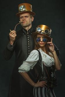 Para steampunk. mężczyzna z fajką i kobieta w okularach i kapeluszu.