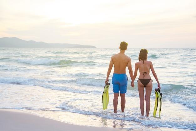 Para stoi na plaży o zachodzie słońca.
