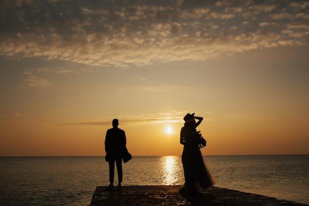 Para stojąc nad brzegiem morza na piękny zachód słońca