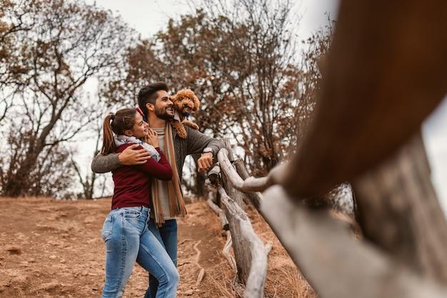Para stojąc w punkcie widzenia i przytulanie. mężczyzna trzyma pudla na ramieniu. jesienny czas,
