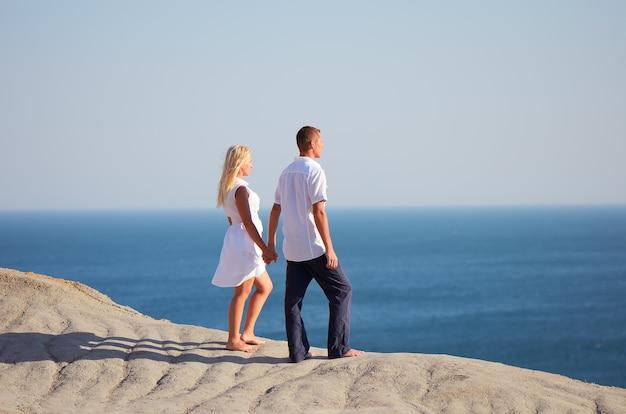 Para stojąca na górze i patrząc na morze trzymając się za ręce