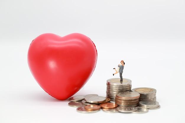 Para stojąca na stosie monet z symbolem serca odczytu, pomysł na zaoszczędzenie pieniędzy dla miłości