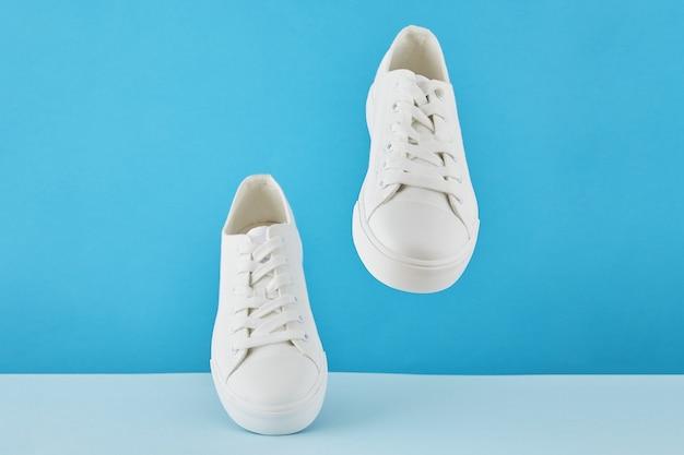 Para stylowych białych trampek moda, buty sportowe do biegania na pastelowym niebieskim tle.