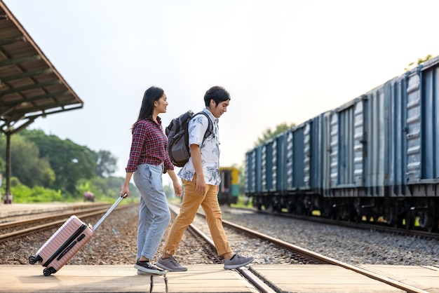 Para stylowych turystów z plecakami i wsiadanie do pociągu na stacji metra na świeżym powietrzu, azjatycka para podróżująca koncepcja stylu vintage na stacji kolejowej, w tajlandii