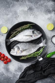 Para surowej ryby dorady lub dorady na patelni grillowej z dodatkami