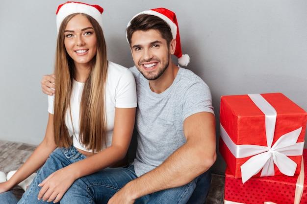 Para świąteczna w pobliżu prezentów