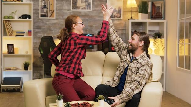 Para świętująca zwycięstwo podczas grania w gry wideo za pomocą kontrolerów bezprzewodowych i przybijania piątki.