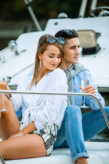 Para świętuje z szampanem na łodzi. atrakcyjny mężczyzna odkorkuje szampana i ma imprezę z dziewczyną na wakacjach. dwóch młodych turystów bawiących się na wycieczce łodzią w okresie letnim