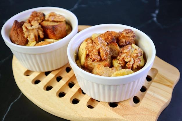 Para świeżego pieczonego budyń z chleba orzechowo-bananowego świeżo pieczone w małej misce na breadboard
