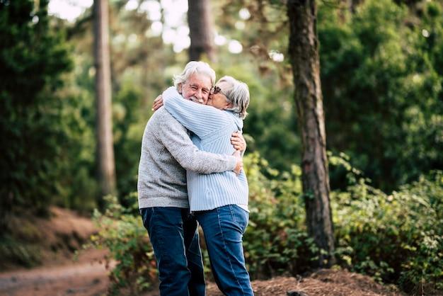 Para szczęśliwych i wesołych kaukaskich seniorów przytula się z miłością i uśmiechem z rozmytym zielonym lasem