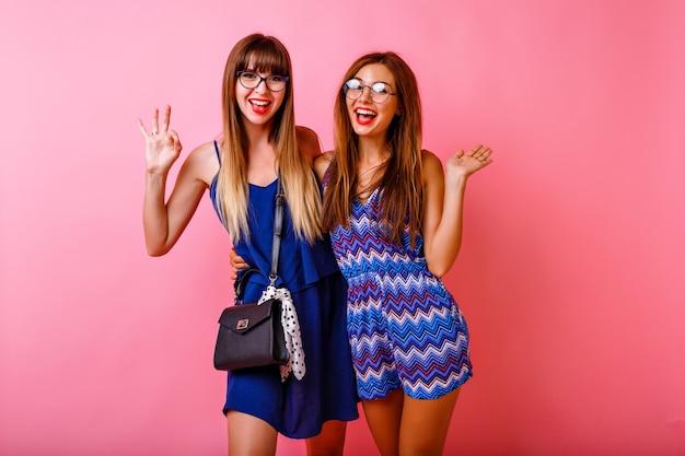 Para szczęśliwych pozytywnie pokonujących przyjaciółek siostrzanych dziewczyn pozujących na różowej ścianie, dopasowanych kolorystycznie granatowych modnych strojów, uściski i uśmiechnięte, zaskoczone emocje, dwie damy razem.