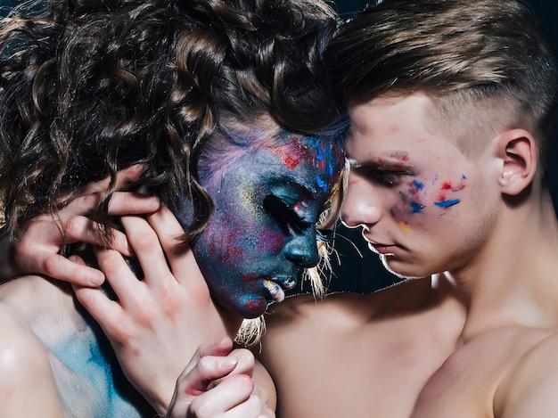 Para sztuki seksualnej czuła młoda para całuje portret sztuka makijaż kobiety z pomalowaną twarz i rzęsy z piór mody