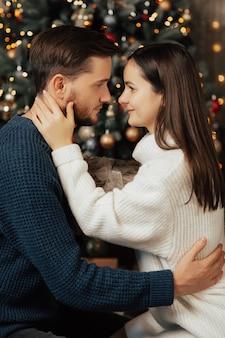 Para szuka siebie i przytulanie. drzewko świąteczne