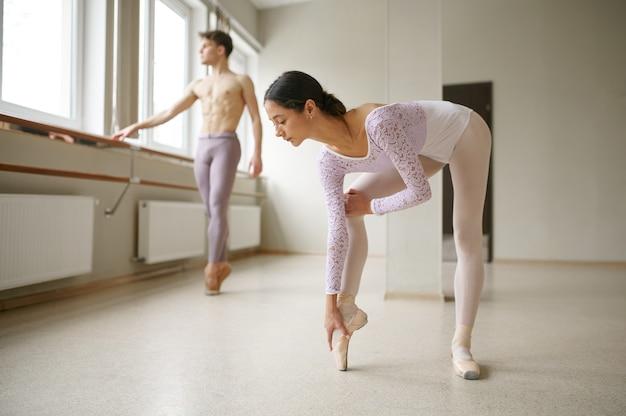 Para tancerzy baletowych robi ćwiczenia rozciągające