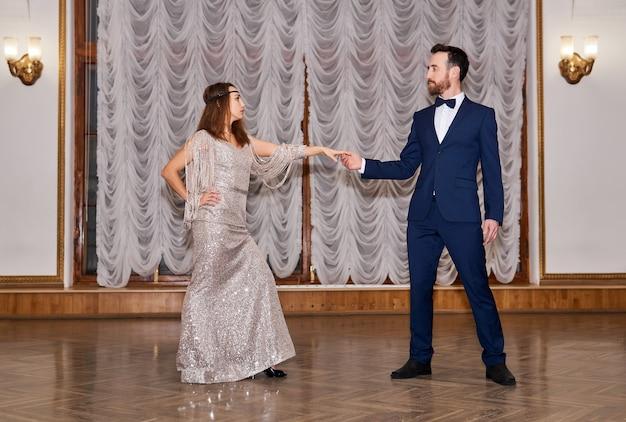 Para tancerzy przed rozpoczęciem tańca partnerskiego w sali vintage; zaproszenie do tańca