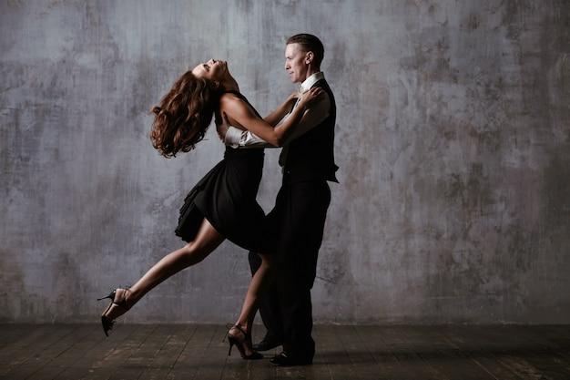 Para tancerzy w czarnej sukience tańczy tango na szarym tle vintage