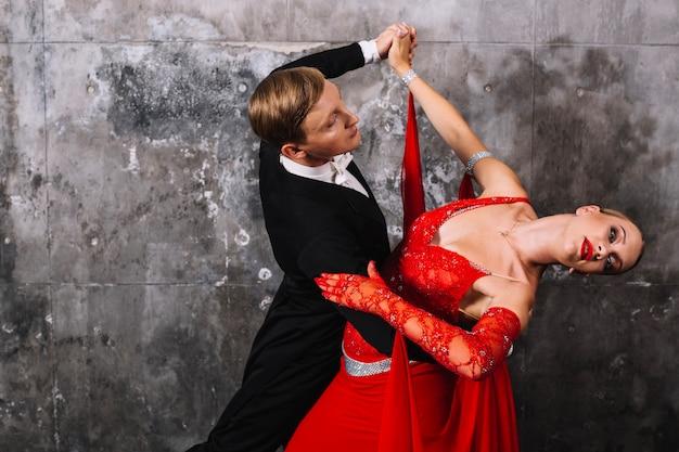 Para tańczy zmysłowy taniec w pobliżu szare ściany
