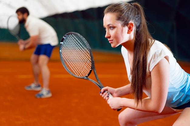 Para tenisistów, mężczyzna i kobieta czeka na usługi na krytym korcie