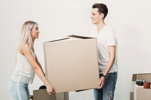 Para trzyma dużego kartonu pudełko