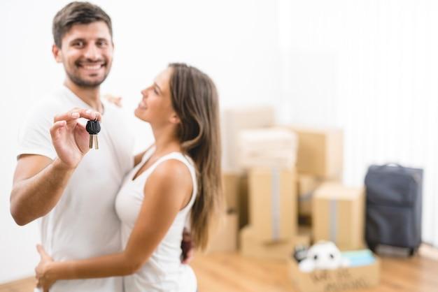 Para trzyma klucze na tle kartonowych pudeł
