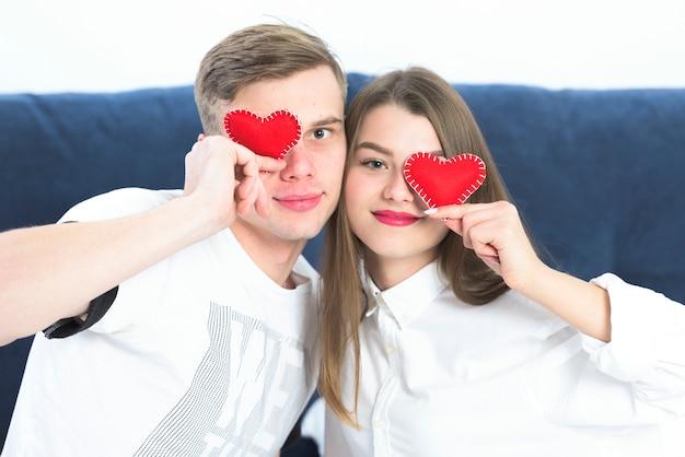 Para trzyma małych zabawkowych serca przy twarzami