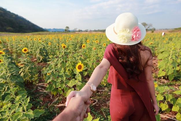 Para trzyma rękę wśród słonecznika pola w naturze