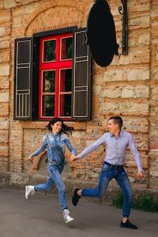 Para trzyma się za ręce i biegnie w pobliżu budynku z pięknym oknem