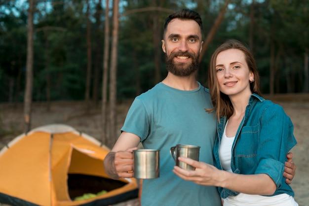 Para trzymając kubki do picia
