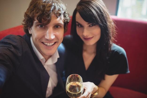 Para trzymając napój i biorąc selfie