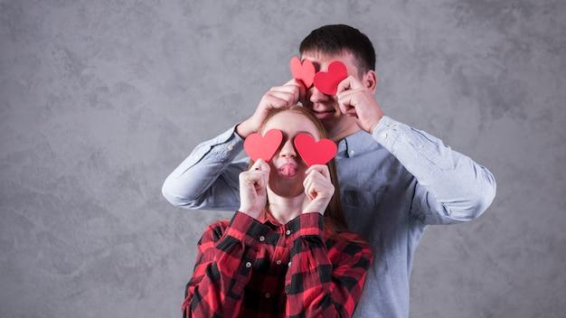 Para trzymając papierowe serca na oczach