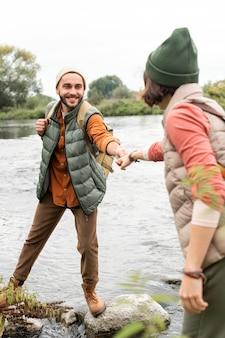 Para trzymając się za ręce i chodząc po skałach