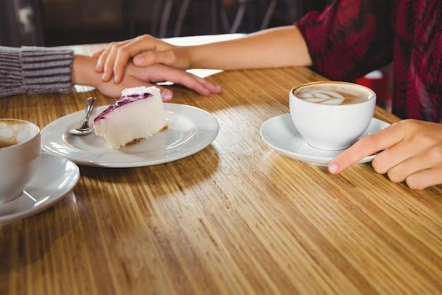 Para trzymając się za ręce i o kawę i ciasto razem