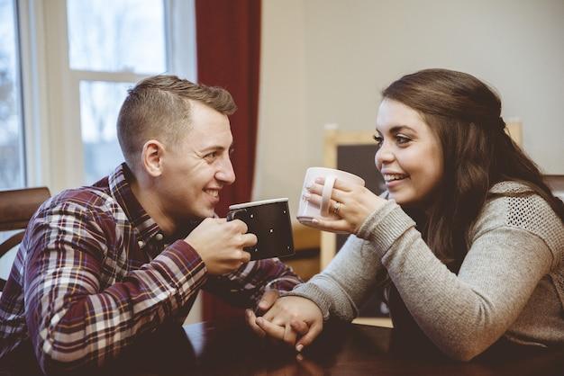 Para trzymając się za ręce i pijąc kawę