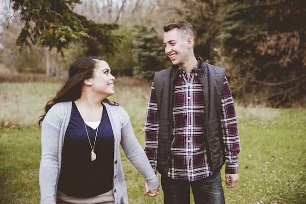 Para trzymając się za ręce i uśmiechając się do siebie podczas spaceru wśród drzew