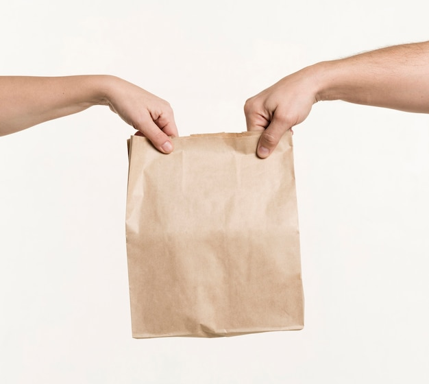 Para trzymając się za ręce papierową torbę