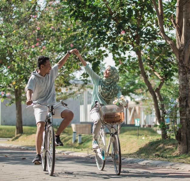Para trzymając się za ręce podczas jazdy na rowerze