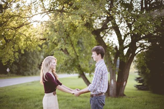 Para trzymając się za ręce w ogrodzie otoczonym zielenią w słońcu