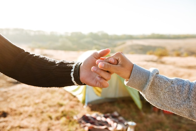 Para trzymając się za ręce w pobliżu namiotu. przycięty obraz