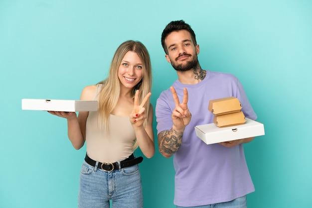 Para trzymająca pizze i hamburgery na odosobnionym niebieskim tle, uśmiechnięta i pokazująca znak zwycięstwa