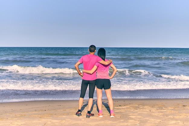 Para trzymająca się naprzeciw morza po treningu rano. ubrana w różową odzież sportową. letni dzień na plaży.
